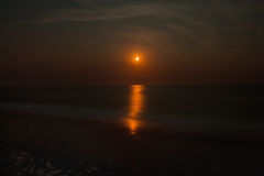 Seascape with a red moon Stock Images
