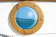 Seascape reflection in sailboat porthole Royalty Free Stock Photography