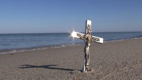 Seascape with religion symbol crucifix in sand stock footage