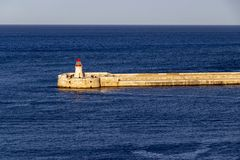 Seascape with the Ricasoli Breakwater Lighthouse at Grand Harbor, Malta. Deep blue seascape with Ricasoli Breakwater Lighthouse at Grand Harbor, Malta Stock Photo