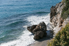 Seascape with rock washed by waves. Shot on sunny day Royalty Free Stock Photos