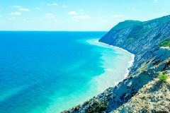 Seascape with rocks, blue sky and Caucasus mountains on the black sea royalty free stock photography