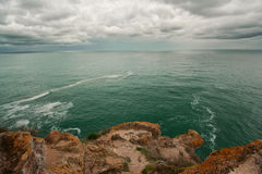 Seascape with rocks and clouds Stock Image