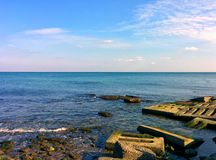 Seascape with rocks and concrete plates. Seascape with coastal rocks and concrete plates Royalty Free Stock Images