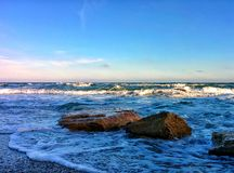 Seascape with rocks and splashes on sea shore Royalty Free Stock Image
