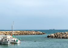 Seascape with rocky beach. Sea pier with boats and yachts stock image