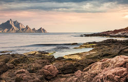 Seascape with rocky coast and mountain ridge with high peaks. Composite landscape with cloudy sky at menacing sunrise royalty free stock image