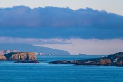 Seascape of rocky headlands, cliffs, homes and a ship along Northern Ireland`s Antrim coast royalty free stock photos