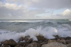 Wavy Sea with a Cloudy Sky. A seascape with a rocky shore, a wavy sea and a cloudy sky Stock Photo