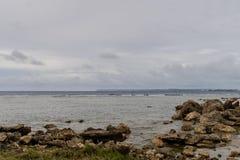 Seascape of rocky shoreline on a cloudy day Stock Photos