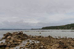 Seascape of rocky shoreline on a cloudy day Royalty Free Stock Photography