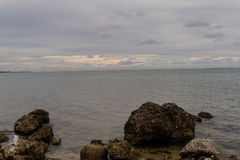 Seascape of rocky shoreline on a cloudy day Stock Image