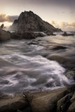 Seascape with rushing water. Scenic view of Sugarloaf rock on coastline with slow motion effect on sea and cloudscape background Royalty Free Stock Images