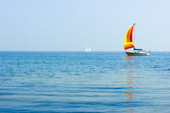 Seascape with sailboat at background of the blue sky. stock images