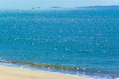 Seascape with sailing boat. Sailing boat can be seen in the distance sailing on the beautiful blue ocean on a hot summers day royalty free stock image