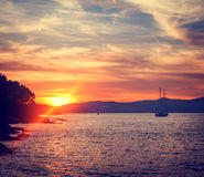 Seascape with Sailing Yacht in Calm Bay at Sunset Royalty Free Stock Image