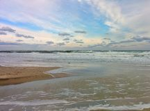Seascape with sand beach, cloudy sky and waves. Sand beach cloudy sky and raging sea Royalty Free Stock Photos