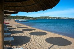 Seascape of a sand beach of Liscia Ruja. With a blue sea and sky of Costa Smeralda and with some beach umbrellas that reflecting their circle shadow on the sand Stock Photos