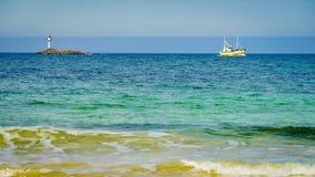 Seascape sandy beach with lighthouse on horizon. Seascape sandy beach sea shore with lighthouse and fishing boat on horizon. Andoya island Bleiksstranda beach stock images