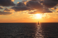 Seascape with setting sun and yacht Stock Photo
