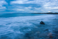 Seascape showing waves forming a mist as they splash against coastal rocks at Plum Point, Jamaica Stock Photos