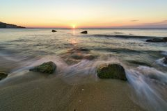 Seascape of Silky sea with rocks against a colorful sky at sunri Royalty Free Stock Photos