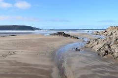 Seascape skały i skała baseny niskiego przypływu i plaży Piasek jest textured i wzorzysty wiatrem i morzem widok zapiera dech w p fotografia stock