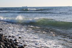 Sea wave and stony shore. Seascape, small waves and blue sea, windless weather Royalty Free Stock Images
