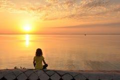 Seascape solnedgång, flickasammanträde på stranden Royaltyfri Foto