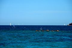 Seascape of some sailing boats in a blue sea. With some rocks and a blue sky as a background stock photo