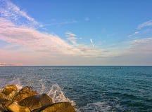 Seascape with splashes and blue sky. Coastal rocks, splashes and cloudy blue sky Royalty Free Stock Photos