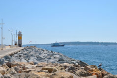 Seascape, stone pier and lighthouse at the port of Marseille Royalty Free Stock Photo