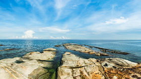 Seascape with stones at the beach and blue sky Stock Image