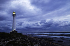 Seascape with storm. A long exposure at sunset on the Atlantic Ocean, South Africa, with the Slangkop lighthouse on the rocky shore and a cloudy sky with an Stock Photo