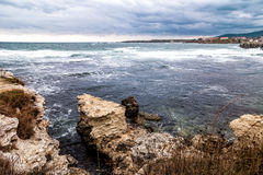 Seascape with stormy clouds and rocks Stock Images