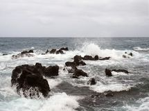 Seascape with stormy dramatic waves breaking over coastal rocks with white surf. And dark water with clouds running to the horizon Stock Photography