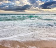 Seascape in stormy weather at cloudy sunrise. Green waves crashing on golden sand of the beach Royalty Free Stock Photo