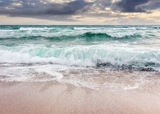 Seascape in stormy weather at cloudy sunrise. Green waves crashing on golden sand of the beach Stock Image