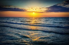 Seascape. Sun in the clouds at sunset over the sea. Royalty Free Stock Image