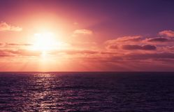 Seascape with sun in dramatic cloudy sky Stock Photos