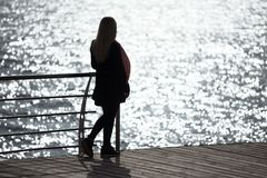 Girl contemplate the sunlight glare in the sea Stock Images