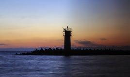Seascape at sunrise, Lighthouse on the coast. Royalty Free Stock Image