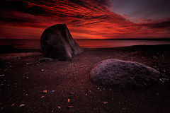 Seascape at sunrise with rich in red color cloud formation Stock Image