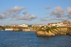 Seascape: sunset lit town on cliffs, blue skies Royalty Free Stock Photo