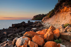 Seascape of Sunset with orange rocks on foreground Stock Photography