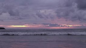 Seascape at sunset reflected on wet beach sand with incoming waves. motor boats with parasailing on a horizon. Seascape at sunset reflected on wet beach sand stock video footage