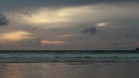 Seascape at sunset reflected on wet beach sand with incoming waves.  stock footage