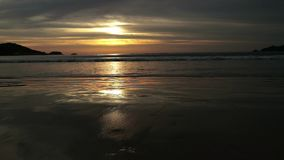 Seascape at sunset reflected on wet beach sand with incoming waves.  stock video