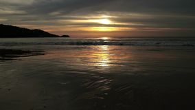Seascape at sunset reflected on wet beach sand with incoming waves.  stock video footage