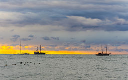 Seascape at sunset time with masted ships Stock Photos